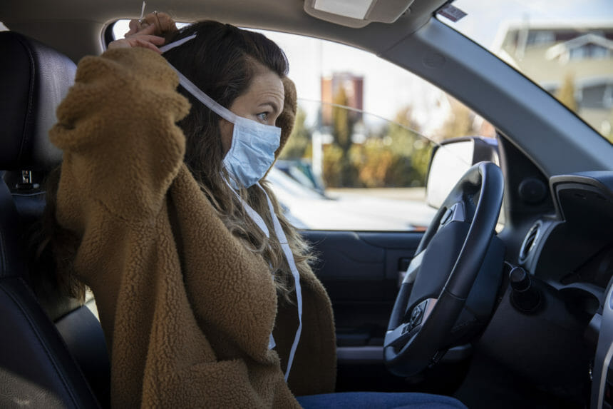 A woman driving her vehicle wearing latex gloves and a mask during the COVID-19 pandemic.