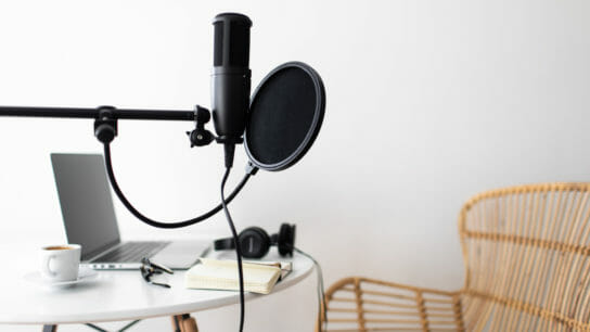 Podcast streaming at home. Audio studio with laptop, microphone with pop filter and headphones on white table.